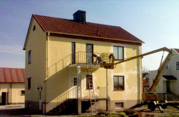 En sjungande målare renoverar sin (?) husfasad vid Endre väg